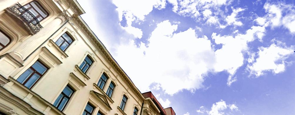 Żółtokremowa kamienica PZG na Białostockiej 4 w Warszawie okiem obserwującego patrzącego w błękitne, zachmurzone niebo.
